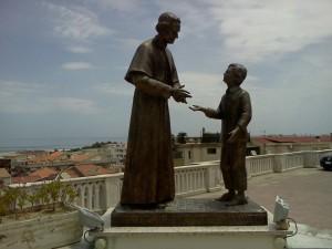 Statua che raffigura Don Bosco con il piccolo Michele Rua