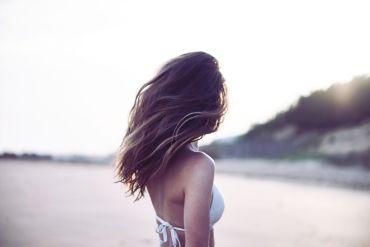 Femme de dos, en maillot de bain sur la plage
