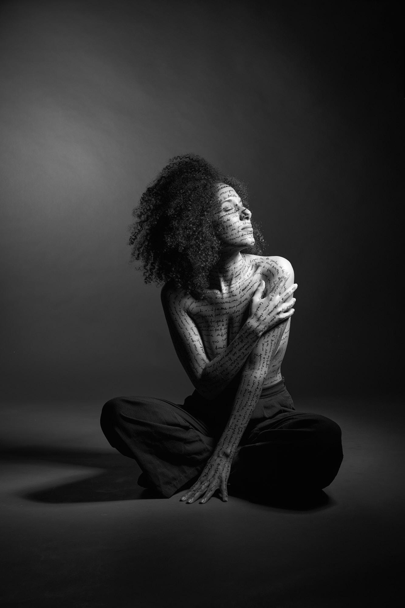 Ue femme assise, écriture sur le corps