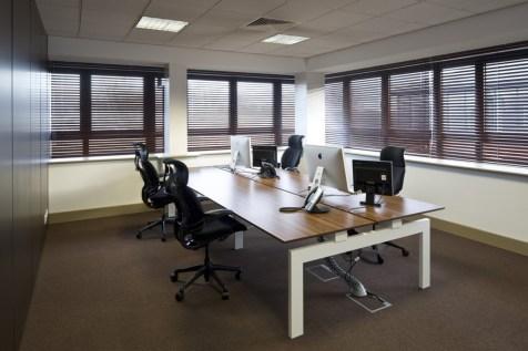Image of Ogilvy 4D back-to-back Steelcase bench desking with oak-effect desktops and ergonomic Herman Miller office chairs