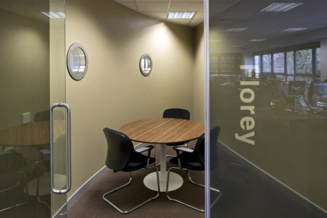 Image of Ogilvy 4D corner office with curved wall, glass door and porthole window details