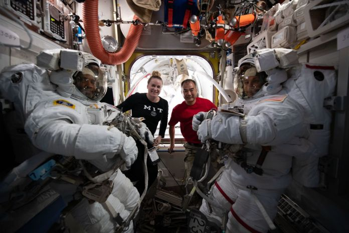 NASA astronaut Mike Hopkins, right, and Victor Glover, right, seen in their spacesuits before the first spacewalk of 2021. NASA astronaut Kate Rubins, in the black shirt, worked with Japanese astronaut Soichi Noguchi, in the red shirt, assisted the spacewalking duo from inside the ISS during both EVAs. Credit: NASA