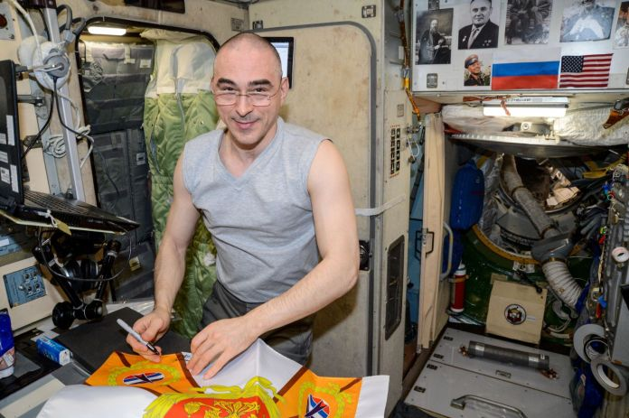 """Expedition 63 Flight Engineer Anatoly Ivanishin works in the """"work compartment"""" of the Zvezda service module in August 2020. The """"transfer chamber"""" is the small tunnel behind him toward the right side of the photo. Credit: NASA"""