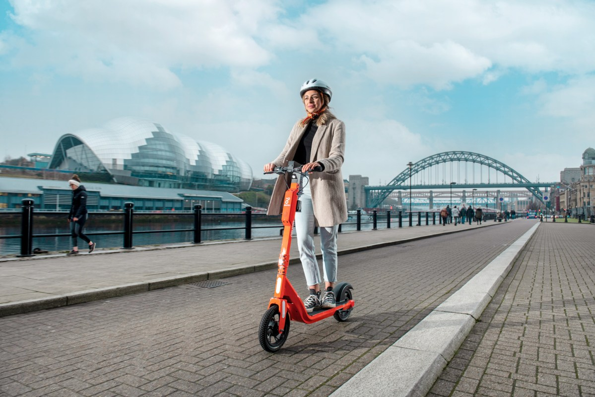 A woman riding an e-scooter