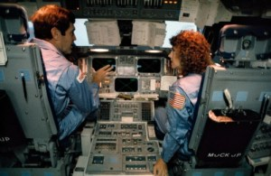 Mission 51L Commander Dick Scobee talks to schoolteacher Christa McAuliffe about the instrumentation of the shuttle's flight deck during pre-launch training (Credits: NASA).