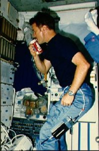An astronaut drinks Coca Cola from a specially designed can which was flown on the shuttle, yet the carbonated space beverage produced unwanted stomach effects in microgravity. Credits: (NASA)