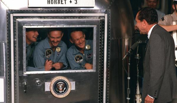 "President Richard M. Nixon welcomes the Apollo 11 astronauts aboard the U.S.S. Hornet, already confined to the Mobile Quarantine Facility (MQF). The quarantine requirement was eliminated following Apollo 14 once it was proven that the Moon was void of pathogens and there was no risk of ""back"" contamination; redits - NASA"