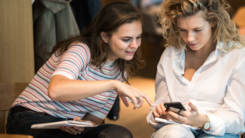 two women in meeting room looking at phone and smiling