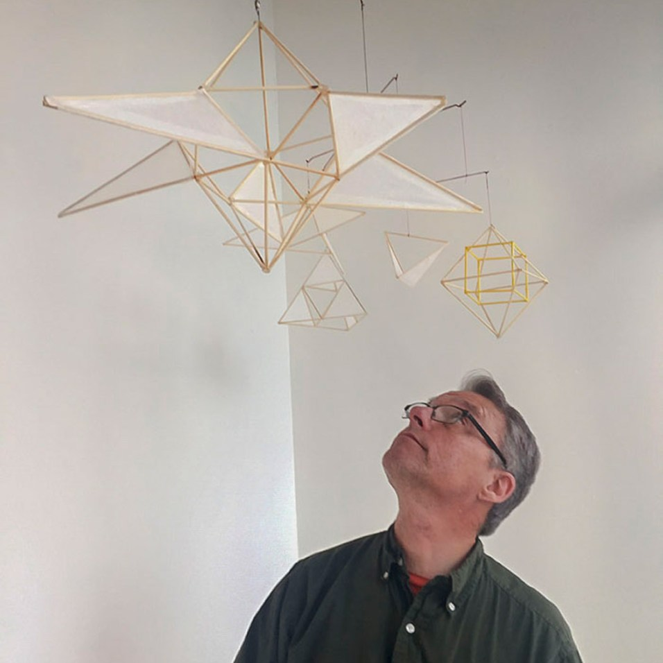 Artscapes alumnus Roger Ralston standing next to his mobile Artscape installation in the Woolworth windows. Photo by Lisa Nappa.