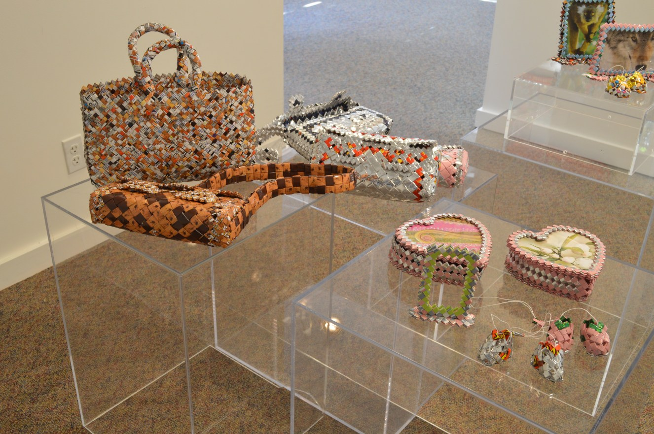 "Works by Pavel Bahmatov: Purses, picture frames, boxes, Ramen wrappers, candy wrappers, and dental floss. ""I was born in Uzbekistan and my family moved to the US as refugees when I was 12 years old in 2004. I got in trouble with the law in 2007 and at 15 years of age got sentenced as an adult to 100 months incarceration. Upon the completion of my sentence I got picked up straight from the correctional facility by ICE, on December-31, 2015 and transferred to NWDC. I am currently being held by ICE at NORCOR facilities in The Dalles, OR and still fighting my battles. I use plastic wrappers from candy, ramen noodles and cookies. Most of the art is woven and then sown with plastic string that we make out of garbage bags. It might not seem like much but if you see that we make all these thing without any tools, like scissors, you will be amazed."" Purses: $75 - $100, Shoes: $25, Picture Frame: $20,and Heart Shapes Jewelry Box: $45"