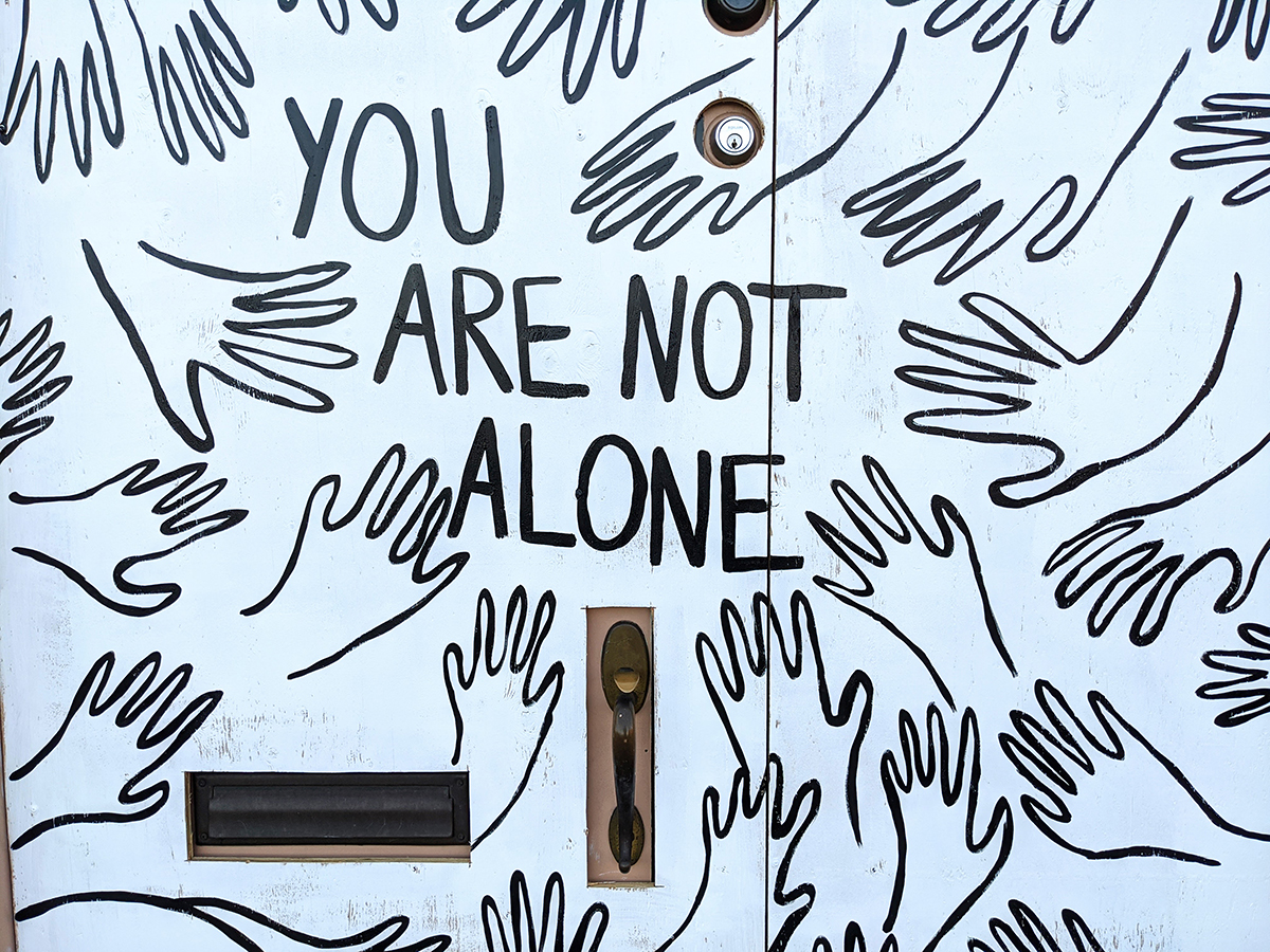 "Multiple line drawing of hands with the words ""you are not alone"""