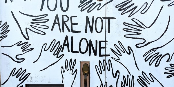 """Multiple line drawing of hands with the words """"you are not alone"""""""