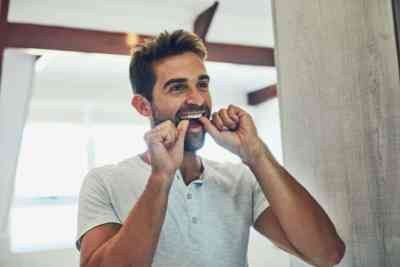 oral hygiene - a man flossing his teeth