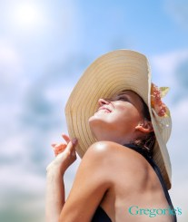 woman with sun hat on sitting in the sunshine.