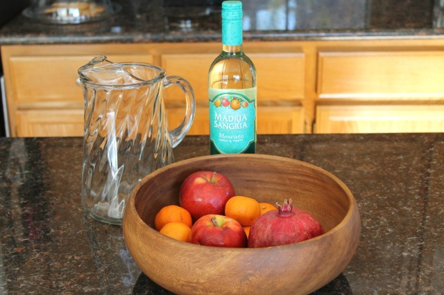 A bottle of Moscato wine, a large glass pitcher, and a bowl of cuties, apples, and a pomegranate on a kitchen counter.