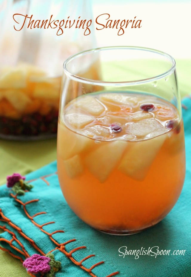 A glass of sangria with mixed fruit on a teal fabric napkin.