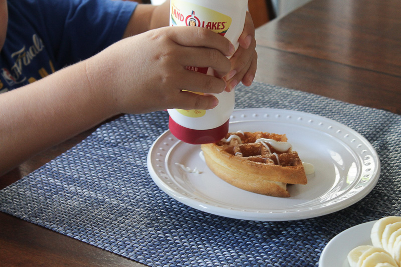A boy's hands squeezing Land O Lakes Soft Squeeze™ Spread onto a waffle.