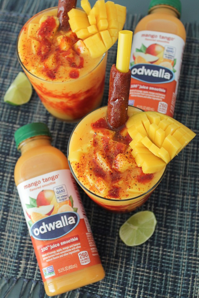 Two mangonada smoothies in glass cups on a blue colored surface with two Odwalla Mango Tango drinks, lime wedges, and a mango slice on the table.