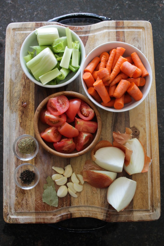 Carrot, celery, tomatoes, yellow onion, garlic, spices prepped for a vegetable broth recipe.
