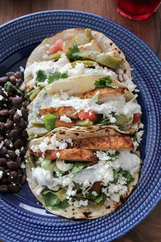 Close-up of three cactus tacos with chicken and cilantro lime Greek yogurt dressing in corn tortillas, served on a blue plate with black beans on the side.