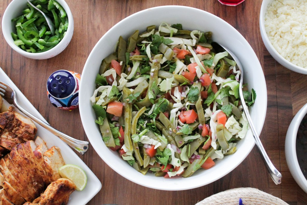 cooked cactus salad with cabbage and tomatoes in a white serving bowl on a dinner table.