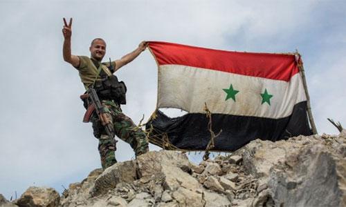 soldado sirio iza la bandera nacional en Alepo