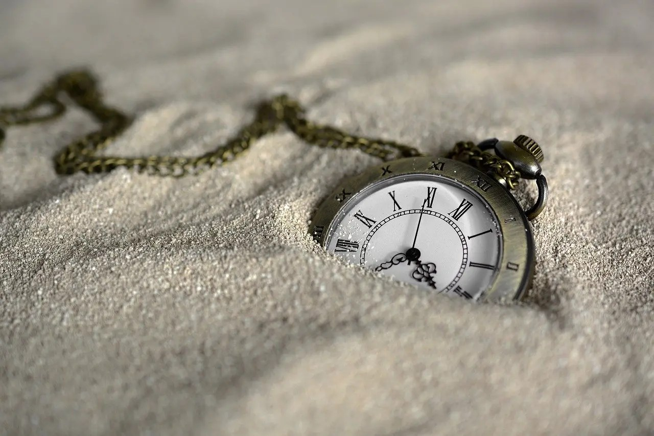 Pocket watch laying on the sand