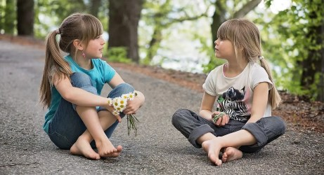 Two blond little girls talking with trees in the back