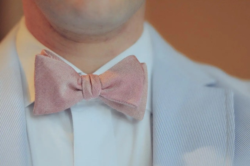 half torso wearing a suite with a bow tie