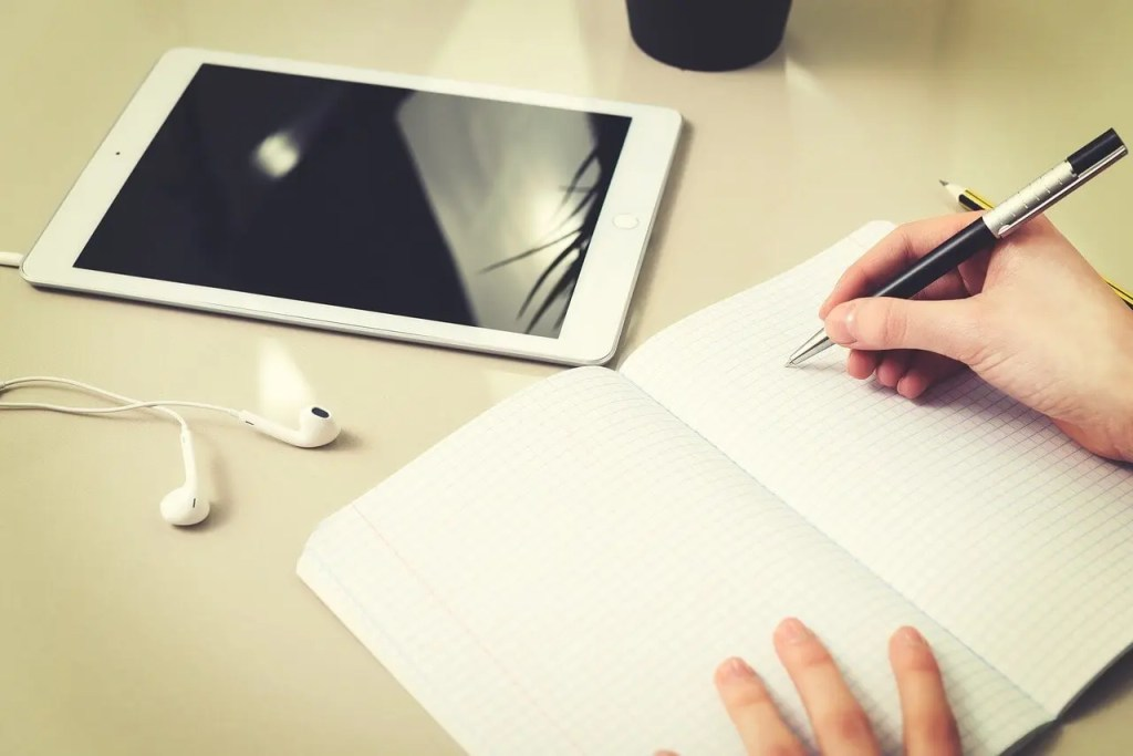 hands writing in notebook next to a tablet