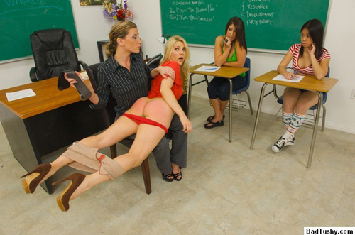 A naughty blonde takes a belt spanking from her teacher infront of the class
