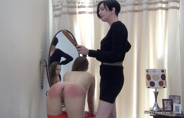 Dana Kane gives bare-bottomed Joelle Barros 100 strokes of the leather paddle