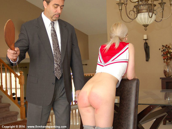 Intern Tara Somerville gets her bare bottom paddled for wearing a sexy cheerleader outfit to work