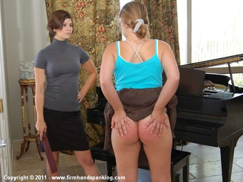 Corinne rubs her sore bottom as Allaura looks on sternly