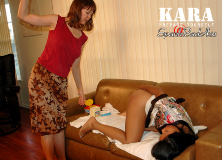 Asian girl bends over for strict spanking on the sofa
