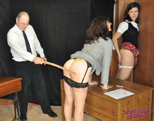 Sarah watches as the principal spanks her teacher with a long, wooden ruler