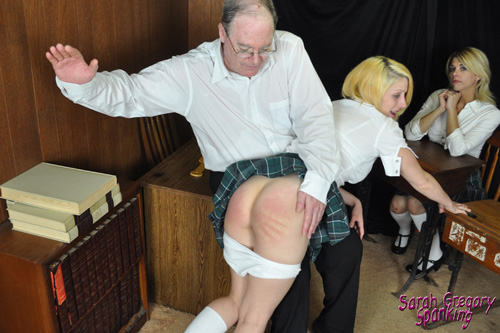 Kat St.James gets a very hard hand spanking by the teacher at the front of the classroom