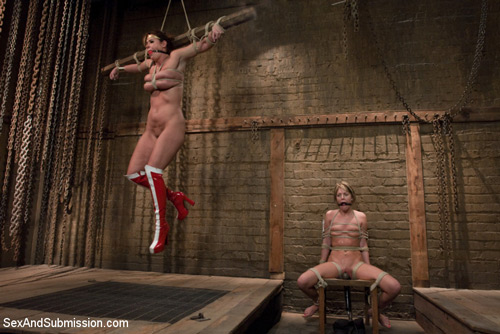 The busty super heroine is tied up naked next to the hostage, Riley Rey