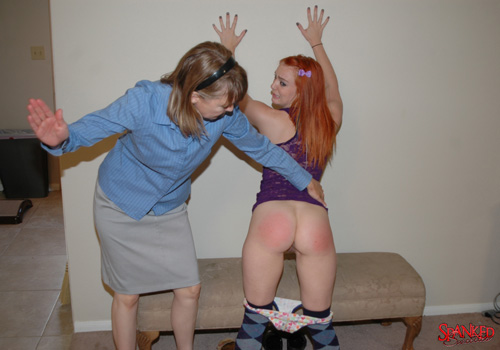 Clare pulls down her panties and spreads Dani's legs for a spanking against the wall