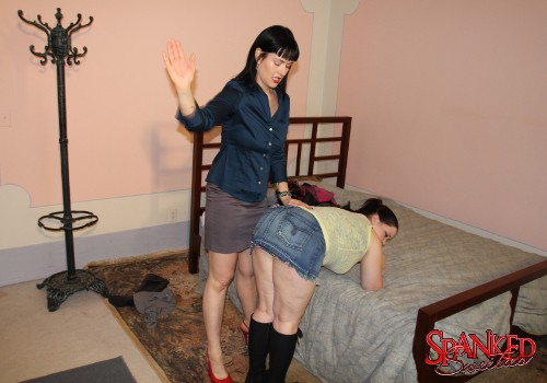 Porcelain bends over the bed for a spanking over her denim skirt
