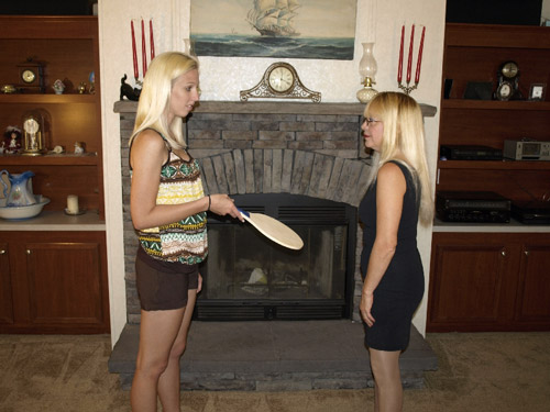 Bryanna hands the big, round paddle to her Aunt Lynn