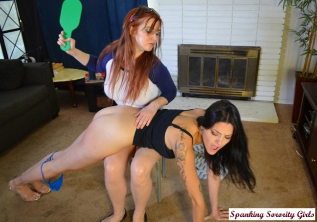 Veronica Ricci paddles Iris's bare bottom with a big green paddle