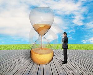 standing-businessman-watching-hourglass-nature-sky-wooden-floor-44509076