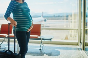 pregnant woman waiting to board plane