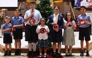Kids holding Jesse Tree symbols