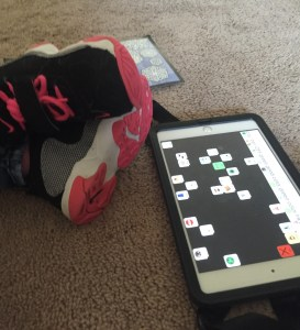 Image is of little feet with stylish sneakers crossed at the ankles by an iPad mini with the Speak for Yourself app. There's a coloring page on the opposite side of the feet.
