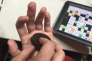 AuthenticAAC moment with image of a chocolate Oreo in a student's hand.