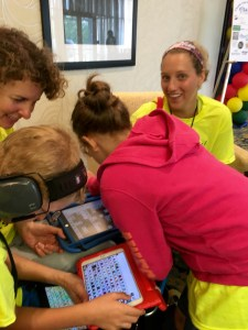 AAC Institute campers looking at their devices, which are iPads with the Speak for Yourself app.