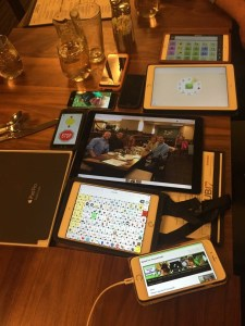 Various iDevices pushed together on a table, each displaying a different app. The center one