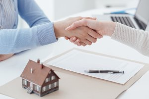 Home loan financing officer and customer shaking hands after signing a contract: real estate home loan